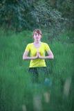 Kvinnan som mediterar i yoga, poserar Royaltyfria Bilder