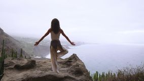 Kvinnan som mediterar i yogakrigare, poserar på havet, sätter på land och vaggar berg Motivation och inspirerande passform och arkivfilmer