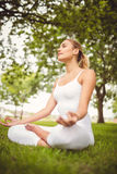 Kvinnan som mediterar med stängda ögon, medan sitta i lotusblomma, poserar Royaltyfria Bilder