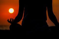 Kvinnan som placerar på en vagga nära havet och, mediterar på gryning på en tropisk ö Royaltyfri Foto