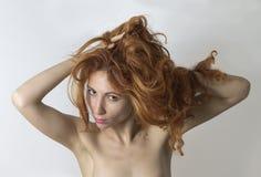 Kvinnan som poserar och, griper hennes röda hår vid händerna Arkivbilder
