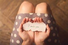 Kvinnan som rymmer en pappers- anmärkning med texten missa jag, dig Royaltyfria Bilder