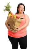 Kvinnan som rymmer en pappers- påse, fyllde med frukt och grönsaker Royaltyfri Bild