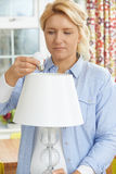 Kvinnan som sätter låg energi, LEDDE lightbulben in i lampan hemma Royaltyfria Foton