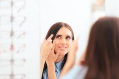 Kvinnan som sätter på medicinskt, kontaktar linser i spegeln arkivfoton