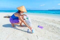 Kvinnan som samlar plast- flaskor p? den h?rliga tropiska stranden, turkoshavet, den soliga dagen som ?teranv?nder rackar ner p?  royaltyfria bilder