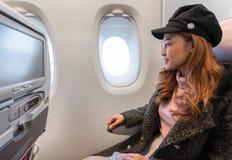 Kvinnan som ser f?nstret av flygplanet tajmar i flykten arkivfoto