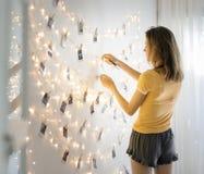 Kvinnan som ser foto som hänger med garnering, tänder på den vita väggen royaltyfri fotografi
