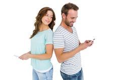 Kvinnan som ser, mans mobiltelefonen Arkivbild