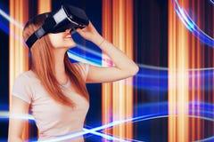 Kvinnan som ser med VR-apparaten, och känsla upphetsar och ler Flicka med exponeringsglas av virtuell verklighet Framtida teknolo Royaltyfri Foto