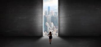 Kvinnan som ser till en cityscape från ett mörkt, tömmer rum royaltyfria bilder