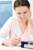 Kvinnan som sitter på en tabell och, skrev Royaltyfri Fotografi
