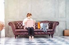 Kvinnan som sitter på soffan rymmer ler hon, en rosa skjorta och royaltyfri foto