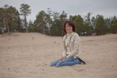 Kvinnan som sitts på strand regnar in Royaltyfri Fotografi