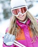Kvinnan som skidåkning med skidar, googlar i vinter royaltyfri fotografi