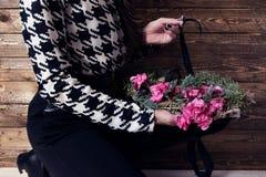 Kvinnan som slår in julkransen med naturliga blommor som är lantliga uppvaktar Fotografering för Bildbyråer