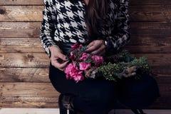 Kvinnan som slår in julkransen med naturliga blommor som är lantliga uppvaktar Arkivbild