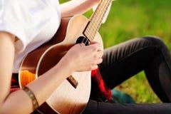 Kvinnan som spelar gitarren, armband p? armen St?ng sig upp fotoet arkivbilder