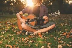 Kvinnan som spelar gitarren parkerar in, på solnedgången Arkivbild