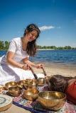 Kvinnan som spelar sjunga, bowlar också bekant som tibetana sjunga bunkar, Himalayan bunkar Framställning av solid massage Royaltyfri Bild