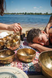 Kvinnan som spelar sjunga, bowlar också bekant som tibetana sjunga bunkar, Himalayan bunkar Framställning av solid massage Royaltyfri Foto