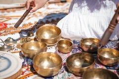 Kvinnan som spelar sjunga, bowlar också bekant som tibetana sjunga bunkar, Himalayan bunkar Framställning av solid massage Royaltyfri Fotografi