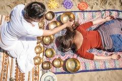 Kvinnan som spelar sjunga, bowlar också bekant som tibetana sjunga bunkar, Himalayan bunkar Framställning av solid massage Arkivbilder