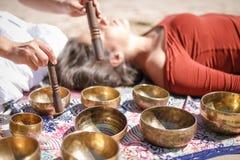 Kvinnan som spelar sjunga, bowlar också bekant som tibetana sjunga bunkar, Himalayan bunkar Framställning av solid massage Fotografering för Bildbyråer