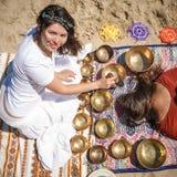 Kvinnan som spelar sjunga, bowlar också bekant som tibetana sjunga bunkar, Himalayan bunkar Framställning av solid massage Royaltyfria Foton