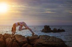 Kvinnan som spelar yoga, poserar på havskust mot härlig solrisin arkivbild