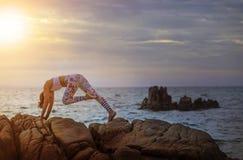 Kvinnan som spelar yoga, poserar på havskust mot härlig solrisin royaltyfri foto