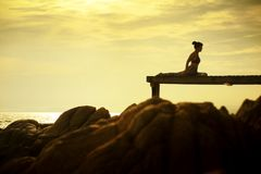 Kvinnan som spelar yoga, poserar på strandpir mot härlig solrisi royaltyfri foto