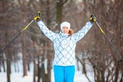 Kvinnan som sportsmanen på argt skidar med, räcker upp Royaltyfri Foto