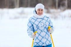 Kvinnan som ståenden med skidar poler räcker in Royaltyfri Foto