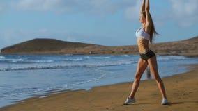 Kvinnan som sträcker ben, och knäsena som gör stående framåt krökningyogaelasticitet, poserar på stranden Konditionkvinna som kop stock video