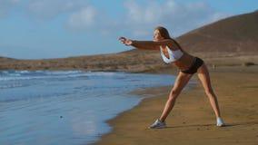 Kvinnan som sträcker ben, och knäsena som gör stående framåt krökningyogaelasticitet, poserar på stranden Konditionkvinna som kop arkivfilmer