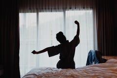 Kvinnan som sträcker i säng efter vak upp, beskådar tillbaka fotografering för bildbyråer