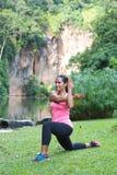 Kvinnan som sträcker tricepbaksida av armen, medan göra utfallet i ett utomhus-, parkerar Fotografering för Bildbyråer