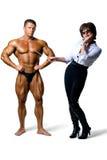 Kvinnan som studerar manlign, förkroppsligar muskulösa manar Arkivfoto