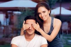 Kvinnan som täcker Man's, synar ta honom vid överraskning på en blindträff royaltyfria foton