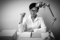 Kvinnan som tänker och, har en penna och en notepad att förläggas Arkivfoton