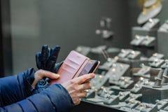 Kvinnan som tar fotoet med mobiltelefonen av vigselringar i smycken, shoppar fönstret Bild med grunt djup royaltyfri fotografi