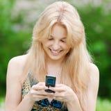 Kvinnan som texting på mobil, ringer Arkivfoton