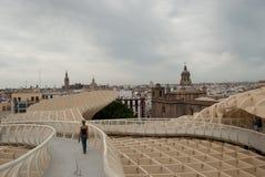 Kvinnan som undersöker de nya arkitekturerna och observerar taken av kyrkorna av Seville på en molnig vårdag royaltyfria foton