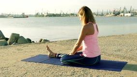 Kvinnan som utför yoga, övar på stranden stock video