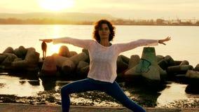 Kvinnan som utför yoga, övar på stranden lager videofilmer