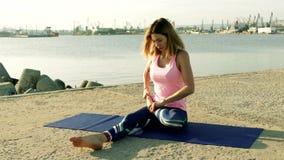 Kvinnan som utför yoga, övar på stranden arkivfilmer