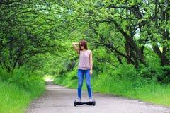 Kvinnan som utomhus rider en elektrisk sparkcykel - sväva brädet, det smarta jämviktshjulet, gyroskopsparkcykeln, hyroscooter, pe Arkivfoton