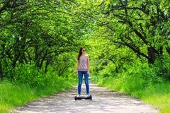Kvinnan som utomhus rider en elektrisk sparkcykel - sväva brädet, det smarta jämviktshjulet, gyroskopsparkcykeln, hyroscooter, pe Arkivbild