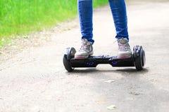 Kvinnan som utomhus rider en elektrisk sparkcykel - sväva brädet, det smarta jämviktshjulet, gyroskopsparkcykeln, hyroscooter, pe Fotografering för Bildbyråer